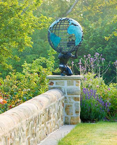 A bronze statue of Atlas, supporting a bespoke brass armillary sphere