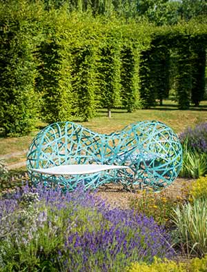 Metal garden bench forged from hundreds of strands of verdigris bronze