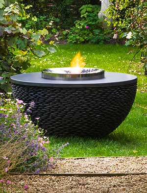 Fire table with black stone hemisphere and a stainless steel pit