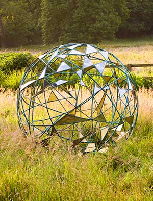 Large garden sphere of two contrasting metals with occasional gold leaf lined plates