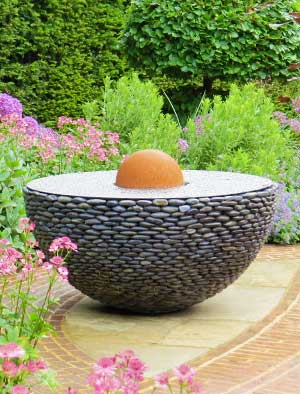 Half garden sphere of black stones with a reflective stainless steel top
