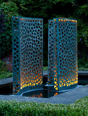 Water wall of verdigris bronze lined with gold leaf