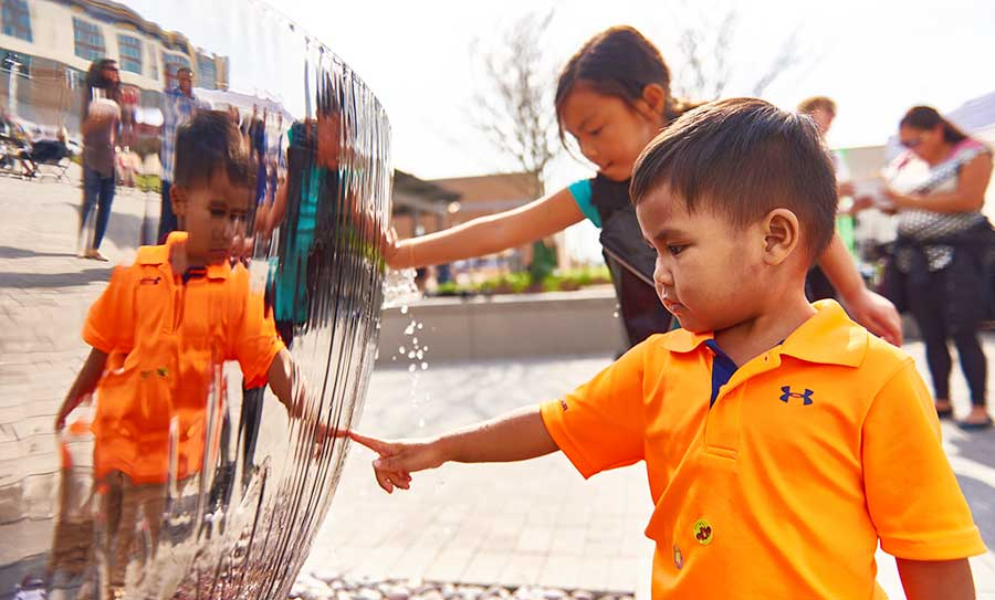 Children interacting with Chalice water feature in public square at the Liberty Center