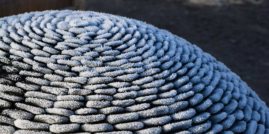 Detail of the frost on a pebble dark planet garden sculpture