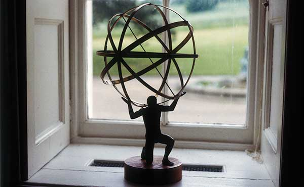 A miniature bronze statue of Atlas, supporting an armillary sphere. Desktop sculpture