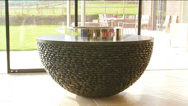 Modern fire table made of black pebbles