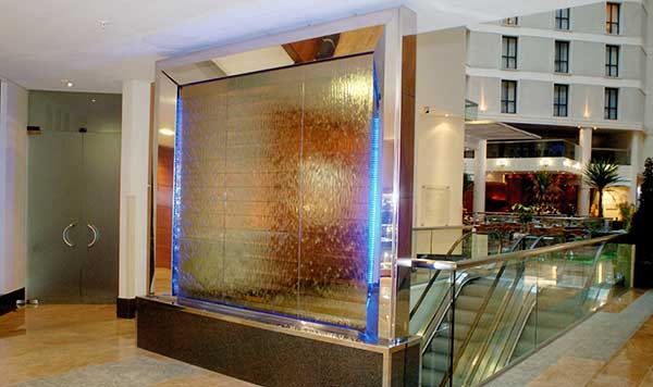 Indoor glass water wall at Gatwick airport. Corporate art