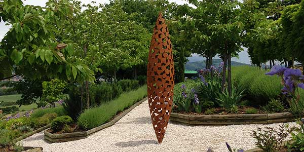 Oxidized steel Quill sculpture in a garden setting