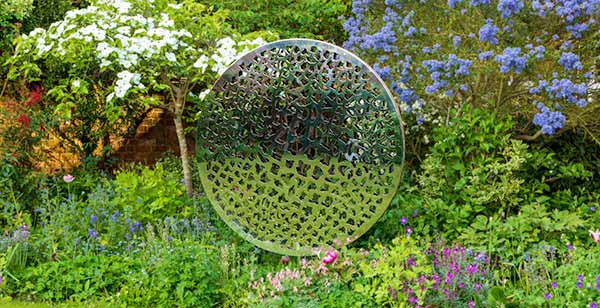 Sculpture made from two parallel circular discs with elaborate laser cut patterns that plays with light and shade