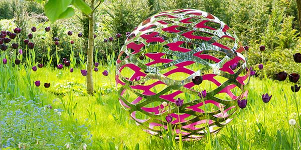 Modern stainless steel sculpture in a beautiful garden setting