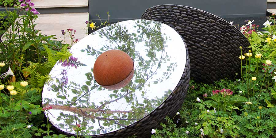 Hemispherical garden sculpture made of pebbles of stainless steel