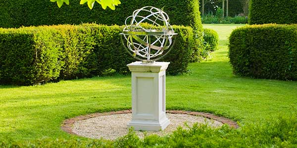 Stainless steel armillary sphere on a white plinth