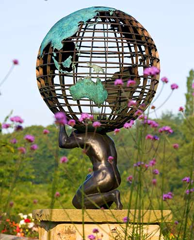 Bronze statue of Atlas supporting a personalised brass armillary sphere in a garden