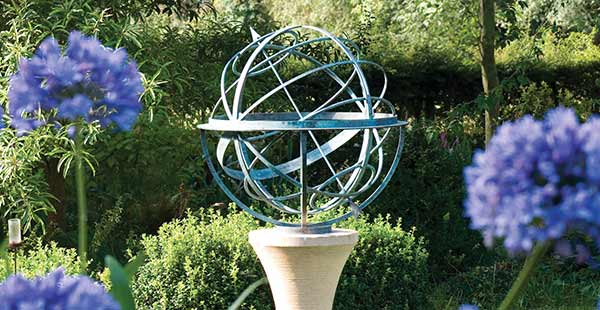 Bronze armillary sphere in contemporary garden