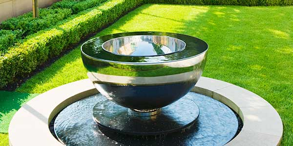 Chalice water feature in a pond in a contemporary garden