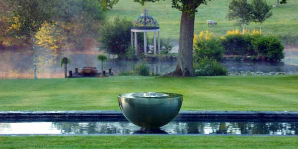 Chalice water feature in a pond in a traditional English garden