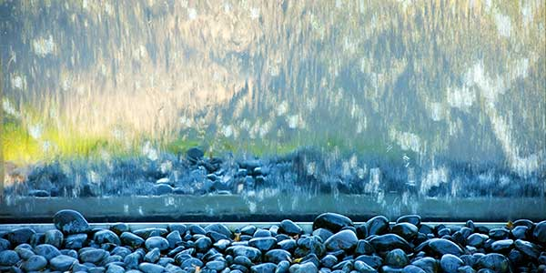 Detail of reflections on the Stainless Steel Water wall and of pebbles at its foot