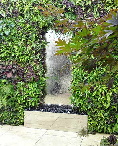 Stainless steel water wall surrounded by planting