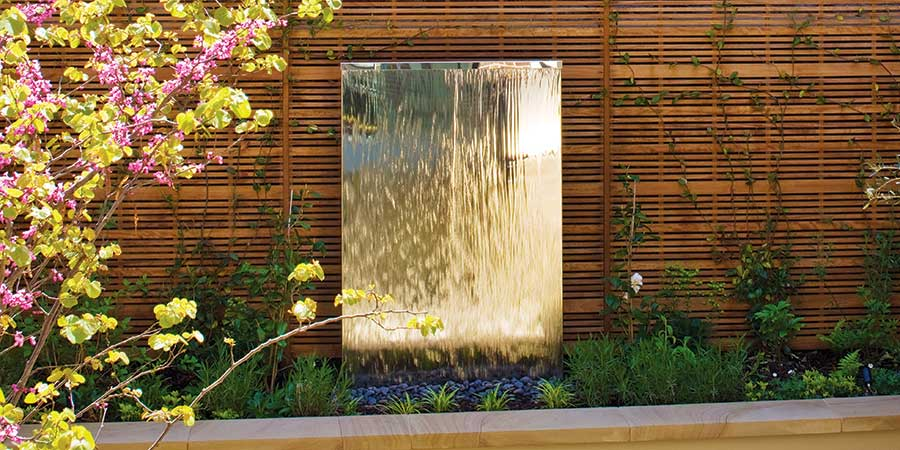 Stainless Steel water wall in a flower bed
